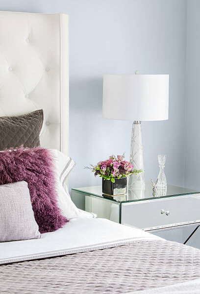 Vertical close-up image of modern, girls bedroom with white leather headboard and side tables.